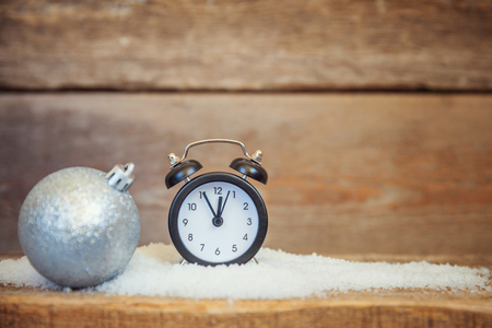 Christmas New Year composition winter objects snow balls alarm clock on old shabby rustic wooden background. Xmas holiday december decoration copy space. Time for celebration concept
