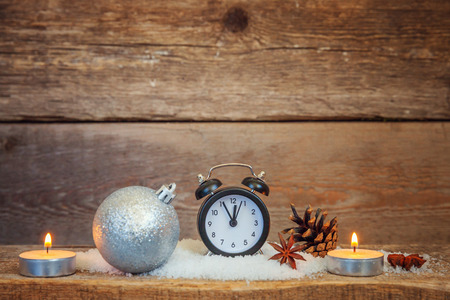 Christmas New Year composition winter objects gift box pine cones balls alarm clock on old shabby rustic wooden background. Xmas holiday december decoration copy space. Time for celebration