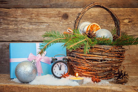 Christmas New Year composition winter objects gift box fir branch basket pine cones balls cinnamon sticks alarm clock on old shabby rustic wooden background Xmas holiday december decoration copy space.