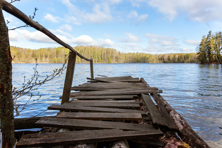 Traditional Russian Finnish and Scandinavian view. Beautiful forest lake or river on sunny summer day and old rustic wooden dock or pier. Fishing bridge on morning lake. Fishing tourism relax concept
