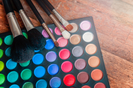Tools for makeup and cosmetics different shades of eyeshadow palette and make up brush on rustic old vintage wooden background. Top view flat lay and picturesque
