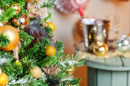 Classic Christmas decorated New year tree. Christmas tree with gold decoration element ball close up. Modern classical style interior design apartment. Christmas eve at home