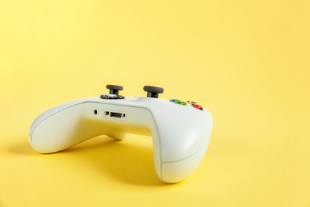 White joystick gamepad, game console on yellow colourful trendy modern fashion pin-up background. Computer gaming competition videogame control confrontation concept. Cyberspace symbol 写真素材