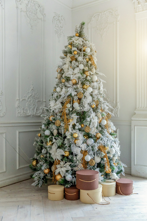 Classic christmas New Year decorated interior room New year tree. Christmas tree with gold decorations and gift boxes. Modern white classical style interior design apartment. Christmas eve at home