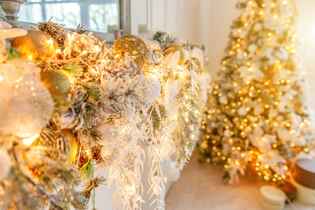 Classic Christmas decorated New year fireplace. Christmas tree with gold decoration element ball. Modern classical style interior design apartment. Christmas eve at home