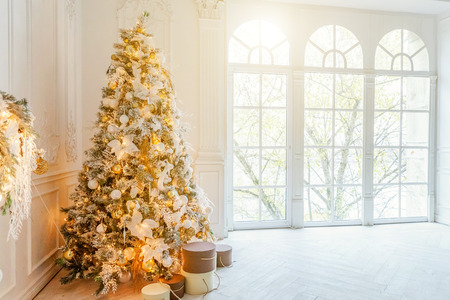 Classic christmas New Year decorated interior room New year tree. Christmas tree with gold decorations. Modern white classical style interior design apartment, large window. Christmas eve at home