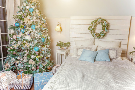 Classic Christmas decorated interior room New year tree. Christmas tree with silver decorations. Modern white classical style interior design apartment bedroom with bed. Christmas eve at home Stok Fotoğraf
