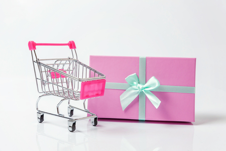 Small supermarket grocery push cart for shopping toy with pink gift box isolated on white background. Sale buy mall market shop consumer concept. Copy space