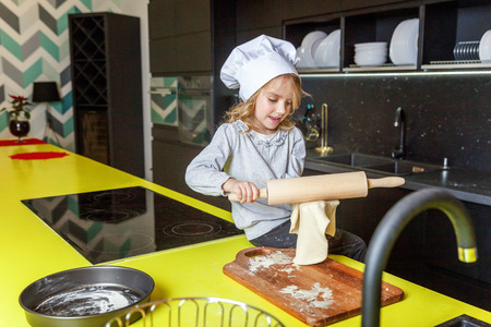Little girl with chef hat, rolling pin preparing dough, bake homemade holiday apple pie in kitchen. Kid cooking healthy food at home and having fun. Childhood, household, teamwork helping concept