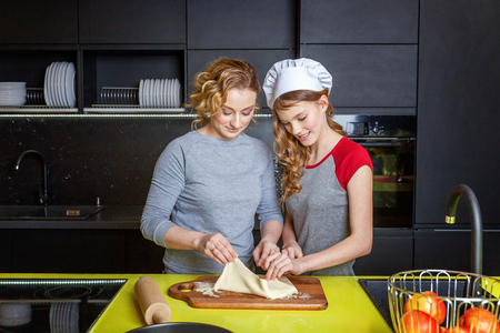 Woman and teenage girl preparing dough, bake homemade apple pie in kitchen. Happy family mother and daughter cooking healthy food at home and having fun. Household, teamwork helping, maternity concept