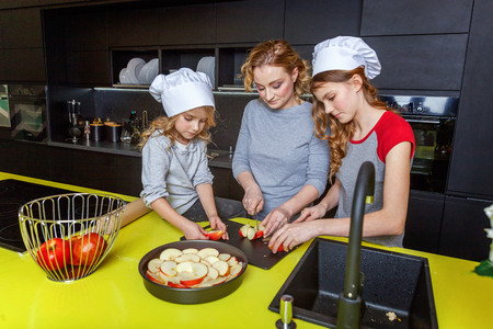 Happy family in kitchen. Mother and two children preparing dough, bake apple pie. Mom and daughters cooking healthy food at home and having fun. Household, teamwork helping, maternity concept 版權商用圖片