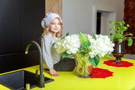 Little girl with chef hat learning cooking smiling in kitchen. Kid preparing healthy food at home and having fun. Childhood, food, healthy eating, household, teamwork, helping, family concept