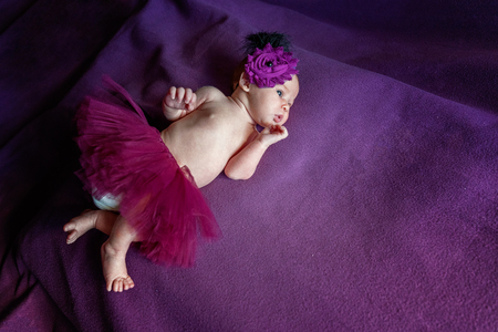Soft portrait of peaceful sweet newborn infant baby lying on bed while sleeping in purple blanket background. Sweet dream, good night. Maternity family childhood innocence care concept Imagens