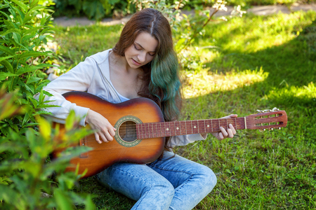 Young hipster woman sitting in grass and playing guitar on park or garden background. Teen girl learning to play song and writing music. Hobby, lifestyle, relax, Instrument, leisure, education concept Standard-Bild