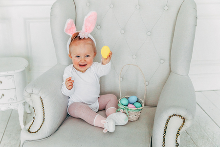 Little child girl wearing bunny ears on Easter day. Girl holding basket with painted eggs at home decoration, having fun on Easter egg hunt. Happy Easter holiday celebration spring concept