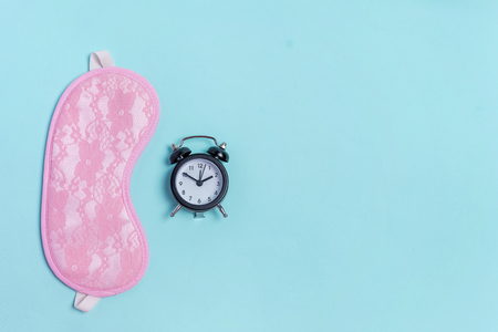 Sleeping eye mask, alarm clock isolated on blue pastel colourful trendy background. Do not disturb me, let me sleep. Rest, good night, siesta, insomnia, relaxation, tired, travel concept
