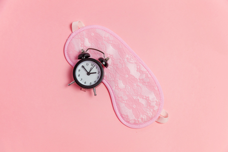Sleeping eye mask, alarm clock isolated on pink pastel colourful trendy background. Do not disturb me, let me sleep. Rest, good night, siesta, insomnia, relaxation, tired, travel concept