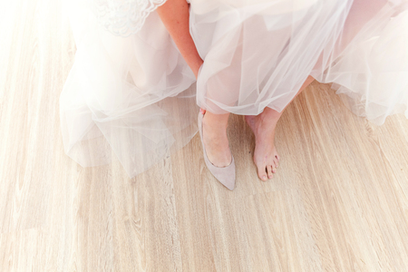 Bride prepare for ceremony wearing beautiful shoes on foot in wedding day. Declaration of love, spring. Wedding morning moments details concept Standard-Bild