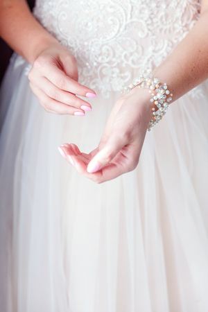 Wedding details and accessories. Bridal preparation, bride putting on jewelry, focus on pearl bracelet. Woman have final preparation for wedding ceremony. Wedding day moments