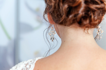 Wedding details and accessories. Bridal preparation, bride putting on jewelry, focus on pearl earring. Woman have final preparation for wedding ceremony. Wedding day moments