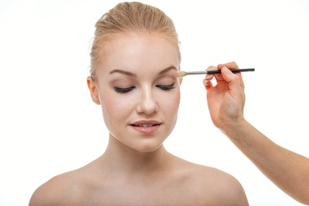 Hand of makeup master applying eyeshadow for young woman model on white background. Professional make up applying by artist. Beautiful girl face with perfect skin. Make-up detail in process 스톡 콘텐츠