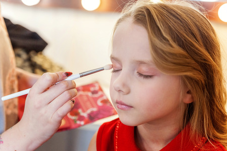Hand of makeup master applying eyeshadow for little pretty girl model. Professional make up applying by artist. Make-up detail in process. Fashon kid beauty salon photosession concept 스톡 콘텐츠