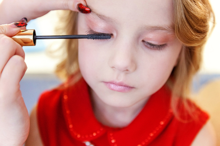 Hand of makeup master applying mascara for little pretty girl model. Professional make up applying by artist. Make-up detail in process. Fashon kid beauty salon photosession concept
