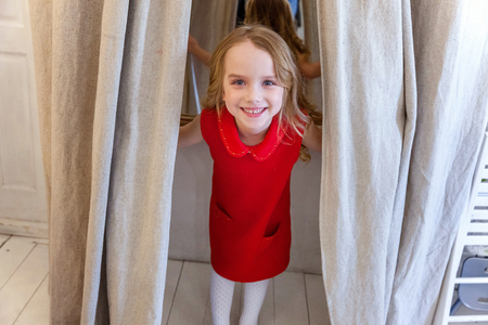 Sweet happy adorable fashion young little girl in red dress standing in light bright room, smiling and laughing. Childhood, schoolchildren, youth, relax concept