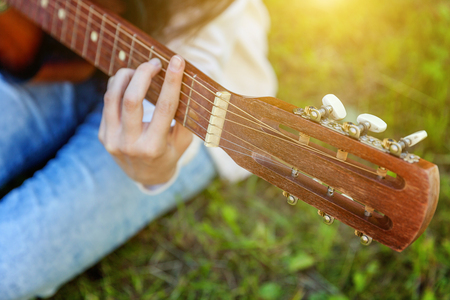 Closeup of woman hands playing acoustic guitar on park or garden background. Teen girl learning to play song and writing music. Hobby, lifestyle, relax, Instrument, leisure, education concept 스톡 콘텐츠