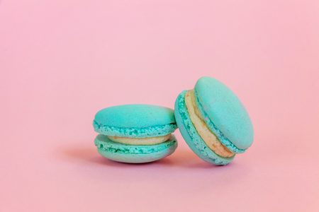 Sweet almond colorful unicorn blue macaron or macaroon dessert cake isolated on trendy pink pastel background. French sweet cookie. Minimal food bakery concept. Copy space
