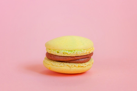 Sweet almond colorful unicorn yellow macaron or macaroon dessert cake isolated on trendy pink pastel background. French sweet cookie. Minimal food bakery concept. Copy space 스톡 콘텐츠