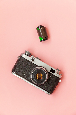 Technology development hipster photographer hobby classic memory trip concept. Vintage film photo camera lens and film roll on pink pastel trendy modern fashion pin-up background