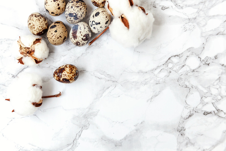 Easter decoration with eggs and cotton on white marble background. Easter concept. Flat lay top view copy space. Spring greeting card