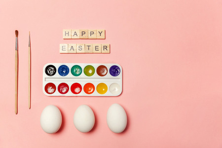 Happy Easter concept. Preparation for holiday. Inscription HAPPY EASTER letters eggs colorful paints isolated on trendy pastel pink background. Simple minimalism flat lay top view copy space Banco de Imagens