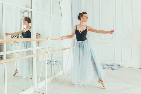 Young classical ballet dancer woman in dance class. Beautiful graceful ballerina practice ballet positions in blue tutu skirt near large mirror in white light hall