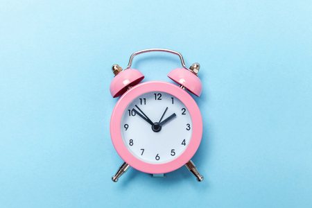Ringing twin bell vintage classic alarm clock Isolated on blue pastel colorful trendy background. Rest hours time of life good morning night wake up awake concept. Flat lay top view copy space Stock Photo