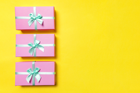 Christmas New Year birthday valentine celebration present romantic concept. Three gift boxes wrapped pink paper isolated on yellow colourful trendy modern background. Flat lay top view copy space Standard-Bild