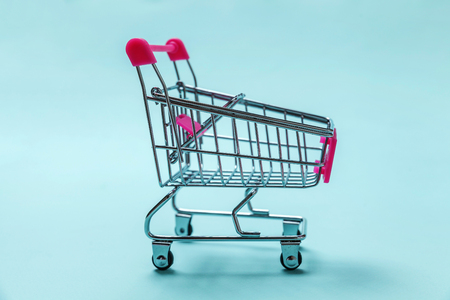 Sale buy mall market shop consumer concept. Small supermarket grocery push cart for shopping toy with wheels isolated on blue pastel colorful paper trendy background. Copy space
