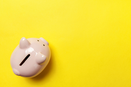 Saving investment budget wealth retirement financial money banking concept. Pink piggy bank isolated on yellow colourful trendy modern fashion background. Flat lay top view copy space 版權商用圖片