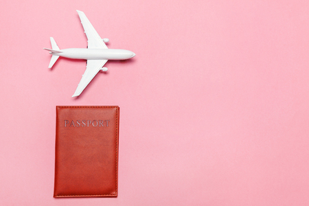 Travel by plane vacation summer weekend sea adventure trip journey ticket tour concept. Minimal simple flat lay with plane and passport on pink pastel trendy modern background Фото со стока