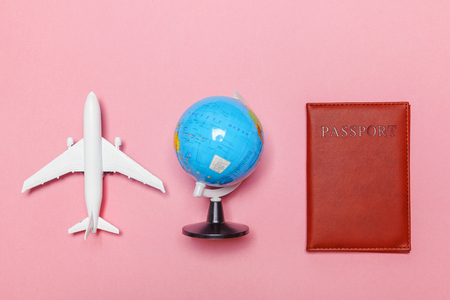 Vacation travel summer weekend sea adventure trip concept. Minimal simple flat lay with plane passport sunglasses and globe on pink pastel trendy modern background