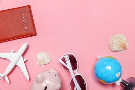 Vacation travel summer weekend sea adventure trip concept. Minimal simple flat lay with plane passport sunglasses globe piggy bank and shell on pink pastel trendy modern background