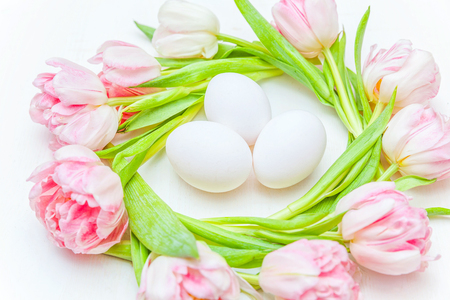Spring greeting card. Easter eggs in nest and pink fresh tulip flowers bouquet on rustic white wooden background. Easter concept. Flat lay top view copy space. Spring flowers tulips Stock Photo