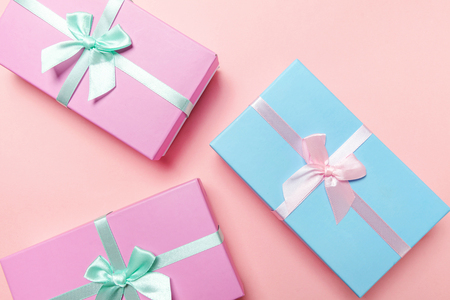 Christmas New Year birthday valentine celebration present romantic concept. Three gift boxes wrapped pink blue paper isolated on pink pastel colorful trendy background. Flat lay top view copy space 免版税图像