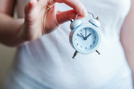 Female woman hands holding ringing twin bell vintage classic alarm clock. Rest hours time of life good morning night wake up awake concept