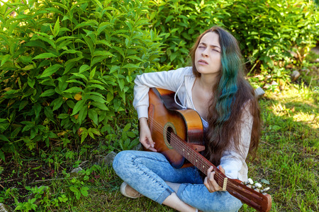 Young hipster woman sitting in grass and playing guitar on park or garden background. Teen girl learning to play song and writing music. Hobby, lifestyle, relax, Instrument, leisure, education concept Stock Photo