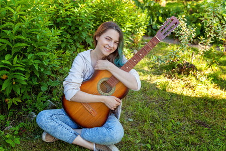 Young hipster woman sitting in grass and playing guitar on park or garden background. Teen girl learning to play song and writing music. Hobby, lifestyle, relax, Instrument, leisure, education concept Imagens