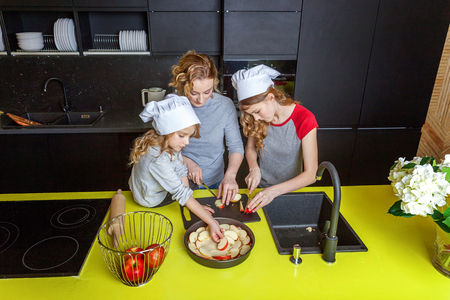 Happy family in kitchen. Mother and two children preparing dough, bake apple pie. Mom and daughters cooking healthy food at home and having fun. Household, teamwork helping, maternity concept Standard-Bild