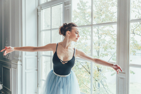 Young classical ballet dancer woman in dance class. Beautiful graceful ballerina practice ballet positions in blue tutu skirt near large window in white light hall Stok Fotoğraf