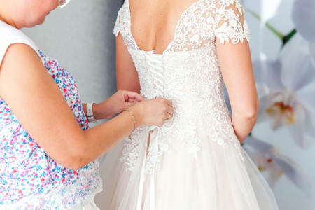Bridesmaid preparing bride for wedding day. Bridesmaid helping bride fasten lacing her wedding white dress before ceremony. Luxury bridal dress close up. Wedding morning moments details concept